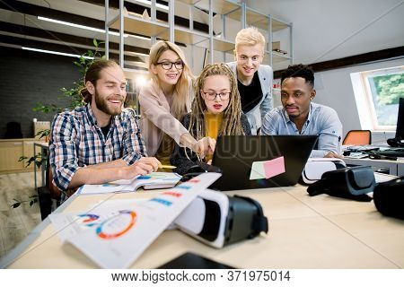 Perfect Multiethnic Creative Team. Group Of Five Excited Cheerful Young People Looking At Laptop Wit