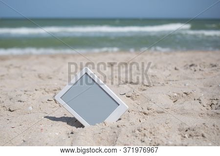 E-book Reader Tablet, White Frame With Grey Screen Sticking Out Of Sand, Beach Vacation Leisure With