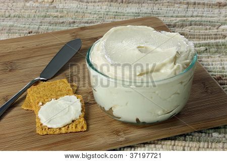 """Homemade Vegan """"Butter"""" in a glass bowl on a bamboo cutting board with crackers and a butter knife poster"""
