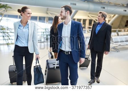 Group of business people as colleagues in airport terminal with luggage on arrival