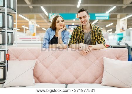 Couple poses at the pink couch in furniture store