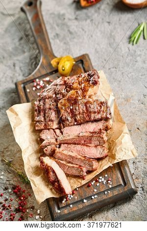 Classic ribeye steak served in waxed paper on wooden cutting board. Cut against grain beef steak. Roasted beef steak with yellow chilli pepper slices and salt crumbs. Rustic spoon and spice bowl