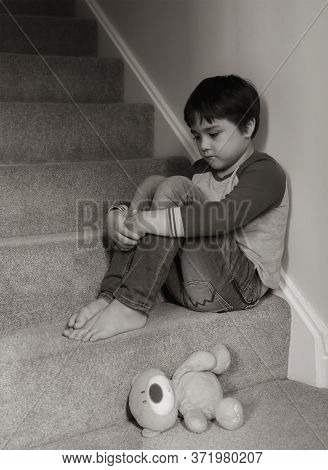Sad Kid Sitting On Staircase With Teddy Bear Lying Down On Carpeted In House, Preschool Boy Looking
