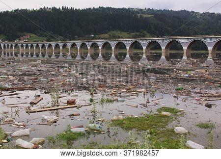 Polluted Water With Plastic Bottle Debris At Bridge Over Bicaz Lake On Bistrita River, Romania. Envi