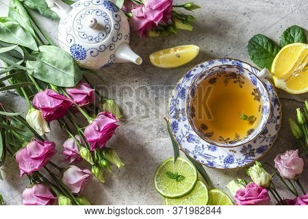 Tea Set, Lemon, Mint And Flowers On A Light Concrete Background. View From Above. Tea Party Concept.