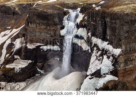 The Haifoss Waterfall Flows Into The Snow Bank Below In Iceland