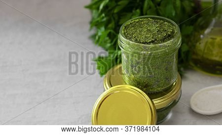 Homemade Pesto With Cashew Nuts In Glass Jar With Mockup Lug Lid, Green Leaves Of Herbs And Olive Oi