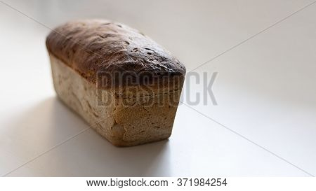 Freshly Baked Crusty Loaf Of Homemade Premium Rye And Wheat Flour Bread On White Table. Contains Glu