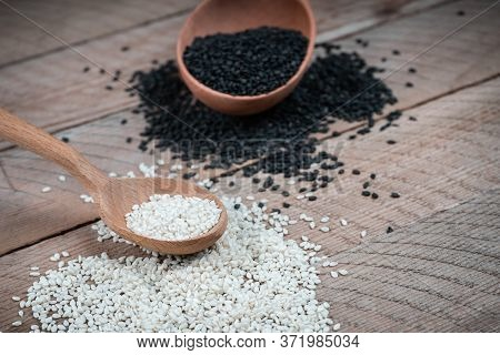 Different Types Of Sesame Seeds. White And Black Sesame Seeds. Seasonings On Wooden Background.