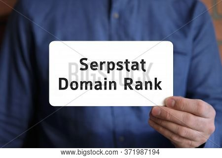 Domain Rank Text On A White Sign In The Hand Of A Man In A Blue Shirt