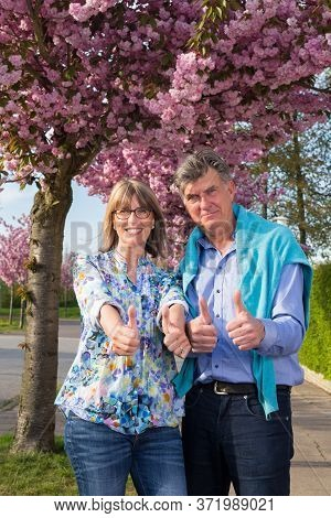 Motivated Positive Senior Couple Giving Thumbs Up.