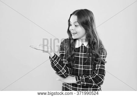Look Here. Product Presentation. Small Girl Nice Hairstyle. Child Long Curly Hair. Happy Schoolgirl