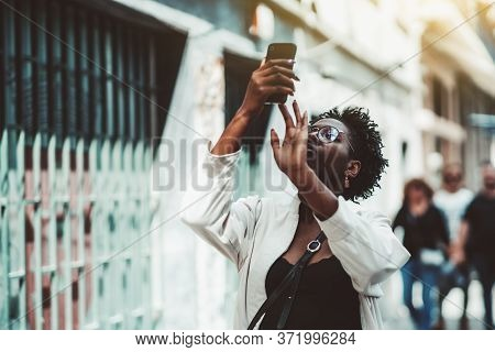 Young Stylish African Female Tourist In Eyeglasses, Top Tank, And A White Trench Is Shooting Sightse