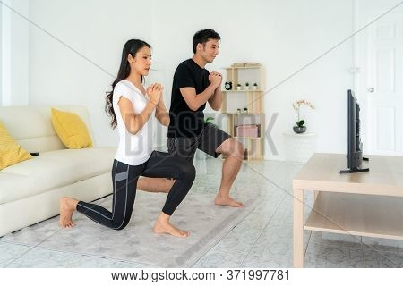 Young Asian Couple Doing Squats Training Together And Looking Tv At Home, Man And Woman Working Out