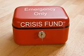 Closed red cash tin marked Crisis Fund - Emergency Only poster