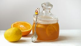 Orange And Lemon Jelly Or Jam In A Glass Jar With Spoon, Lemon And Orange On White Table. Summer Har