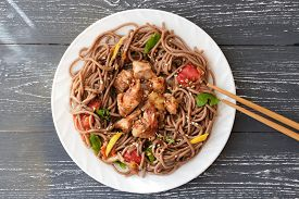 Japanese Buckwheat Noodle Soba With Vegetables, Chicken Meat And Soy Sauce. Chopsticks By The Dish.