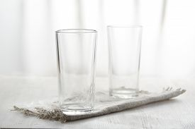 Two Empty Glasses On Linen Napkin On White Background In Blur.