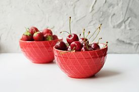 Two Red Bowls With Strawberries And Cherries On A White Table On A Concrete Wall Background.