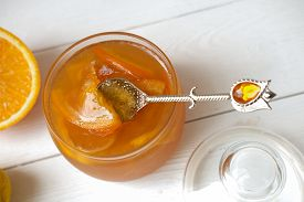Orange And Lemon Jelly Or Jam In A Glass Jar With Spoon, Orange On White Table. Summer Harvesting An