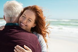 Loving couple embracing at beach with copy space. Portrait of beautiful loving woman hugging senior man at sea with closed eyes. Cheerful couple in love hugging and smiling while relaxing at vacation.