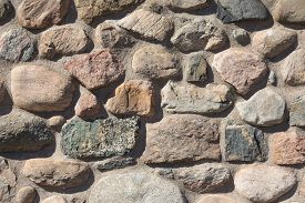 Old Stable Stone Wall With Rows Of Nature Masonry Stones. Brickwork With Individual Craft Bricks Pat