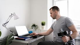 Virtual Workout, Fitness At Home. Athletic Man Watching On Laptop. A Man With A Dumbbell In His Hand