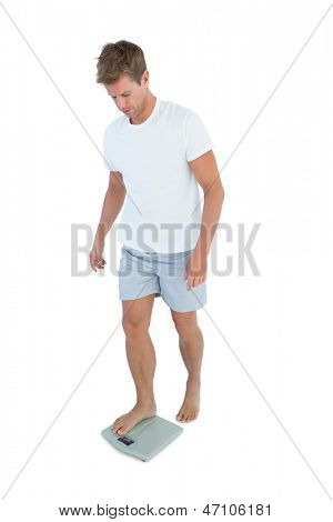 Man getting on a weighing scale on white background