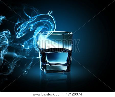 Image of glass of blue cocktail with fume going out