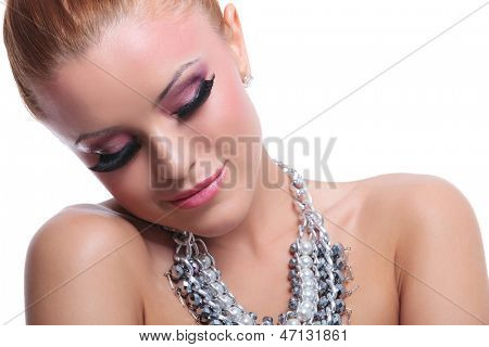 closeup of a young beauty woman looking down while smiling. on background poster
