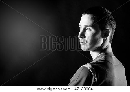 soccer player is looking sideways on black background