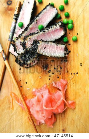 served roasted tuna slices with black sesame and green peas on wooden plate isolated over white background