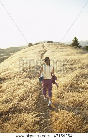 Woman carrying a yoga mat on a dirt path