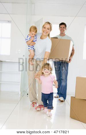 Familia con caja de mudarse a nueva casa sonriendo