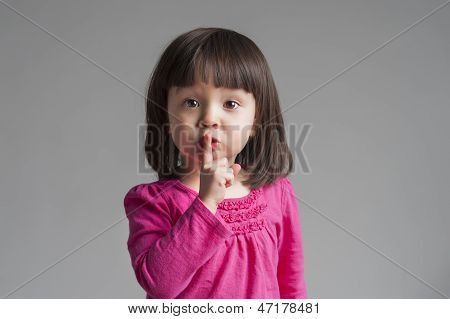 Little girl keeping quiet gesture