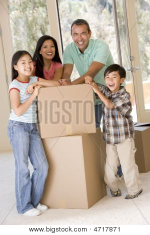 Family With Boxes In New Home Smiling