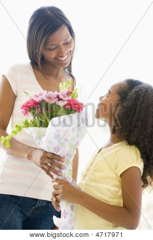 Mother Giving Daughter Flowers And Smiling