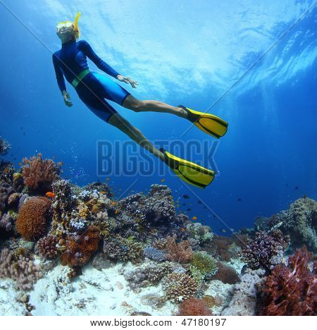 Young woman freediving in a sea over vivid coral reef