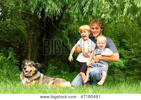 A happy father and his two children sit outside under a willow tree with their dog poster