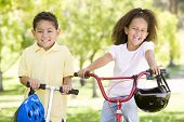 Brother and sister outdoors with scooter and bicycle smiling poster