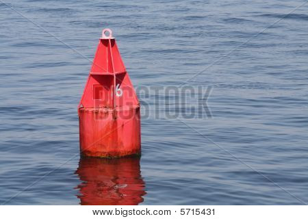 A lonely red buoy floating in calm waters