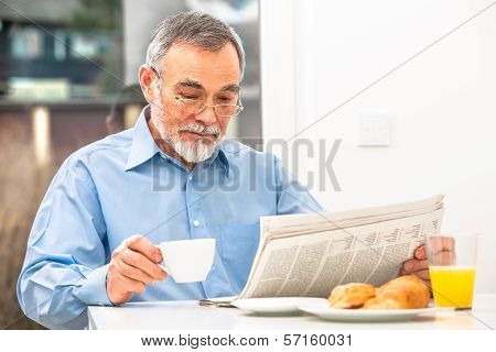 Senior man with glasses reading newspaper at breakfast poster