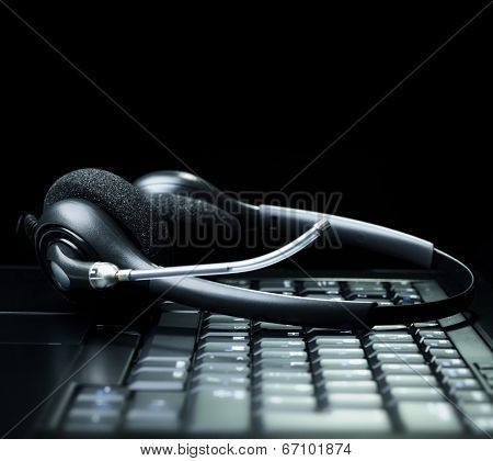 VOIP headset on laptop computer keyboard concept for communication, it support, call center and customer service help desk