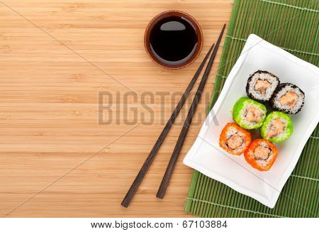 Colorful sushi maki with tobiko on bamboo table with copy space