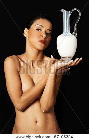 Nude woman is holding a ewer or yug of milk. Spa concept.