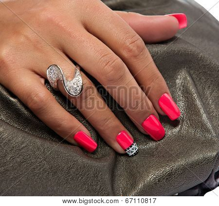 closeup of the woman's hand wearing luxury ring, pink nail art manicure on bronze leather bag background