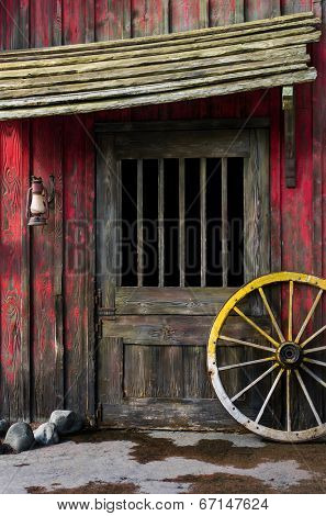 Detail of old wagon wheel next to a wooden wild west typical house