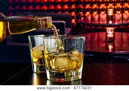 Barman Pouring Whiskey In A Lounge Bar