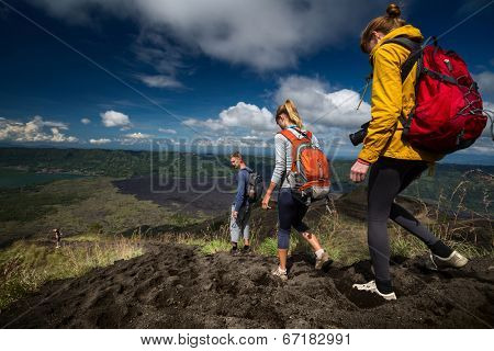Group of hikers descending on friable ground in the caldera of volcano of Batur. Bali, Indonesia poster