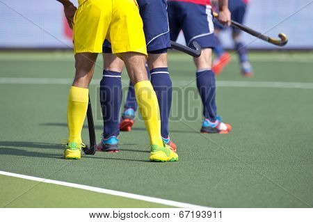Hockey players from two different teams guarding during a match on an artificial grass pitch